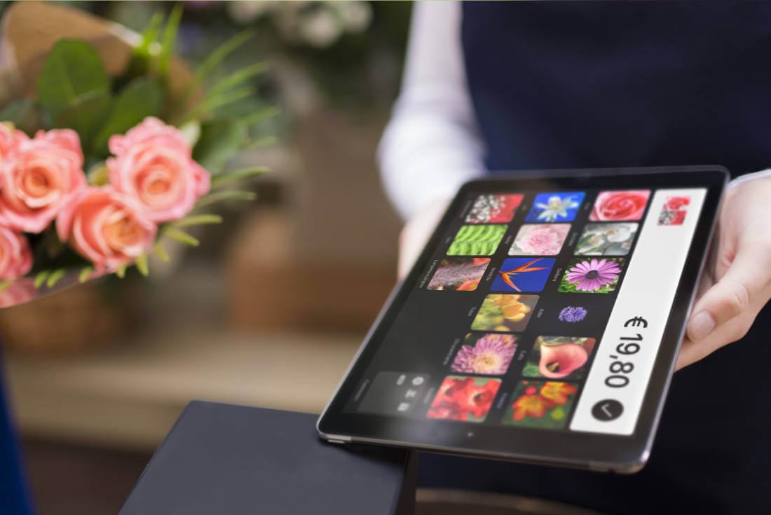 Zwei Hände halten ein iPad mit dem Kassensystem QuickBon auf dem Bildschirm