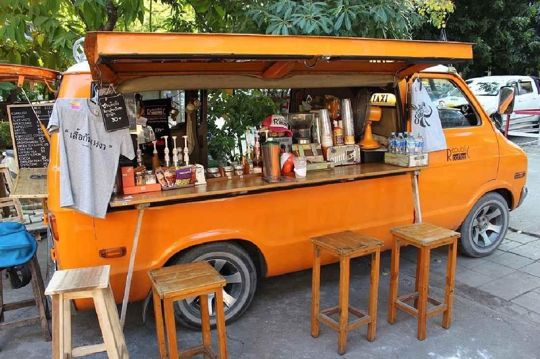 Oranger Food Truck mit Stühlen